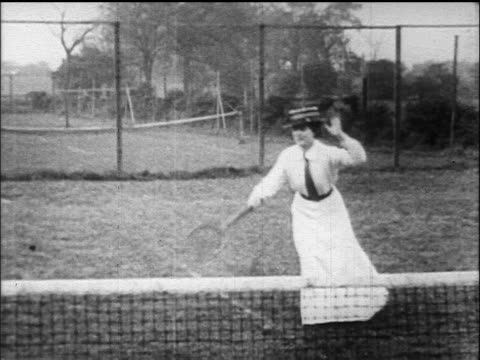 b/w 1900s/1910s woman playing tennis on grass court in hats + long skirt - tennis stock videos & royalty-free footage