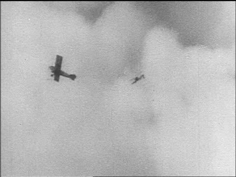 B/W 1910s 2 biplanes flying thru clouds / World War I / newsreel