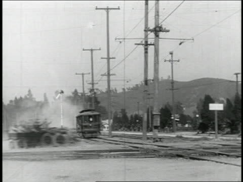 B/W 1910s 2 cars driving across trolley tracks in front of oncoming trolley / feature
