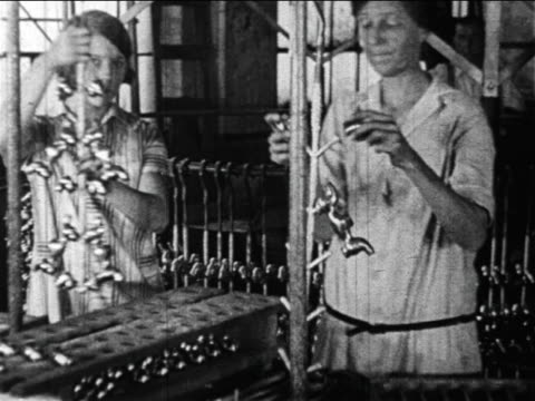 b/w 1910s 2 female factory workers removing metal pieces from molds / newsreel - 1910 stock videos & royalty-free footage