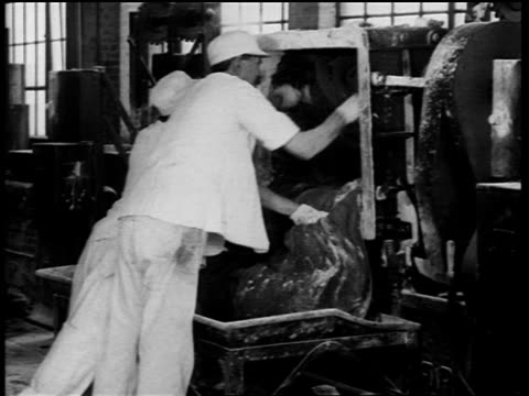b/w 1910s 2 men scraping chewing gum out of machine in chewing gum factory - gomma da masticare video stock e b–roll