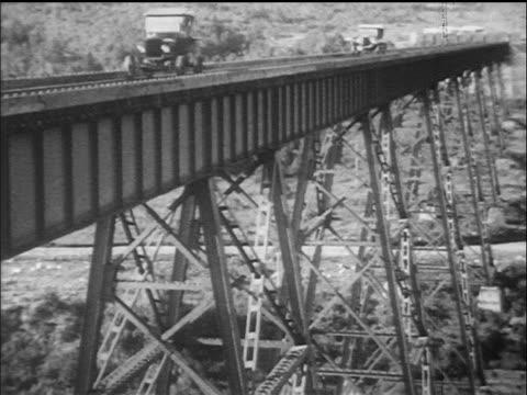 vidéos et rushes de b/w 1910s 2 model t's driving over train bridge / documentary - ford model t