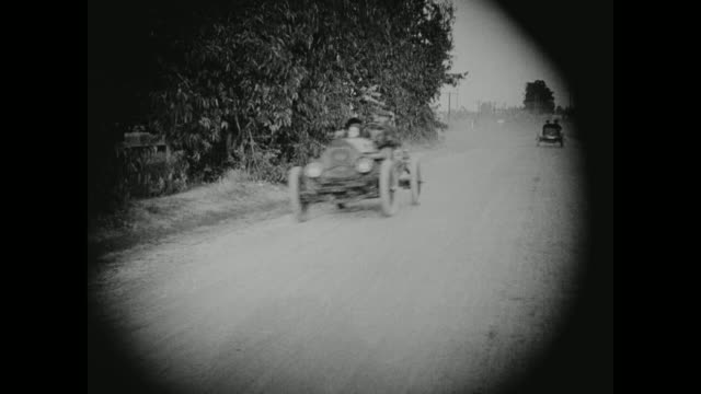 1910s a car speeds down the street - 1910 stock-videos und b-roll-filmmaterial