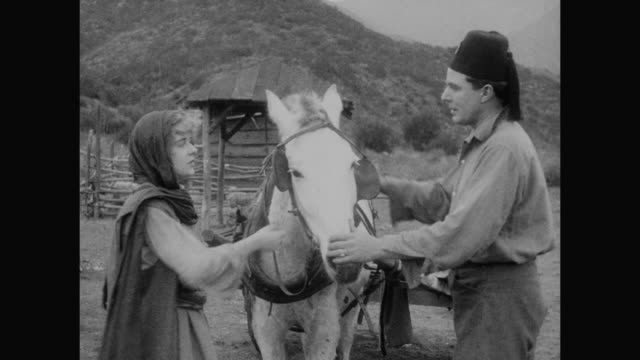 1910s A distrusting woman (Blanche Sweet) instructs man (House Peters) at gunpoint
