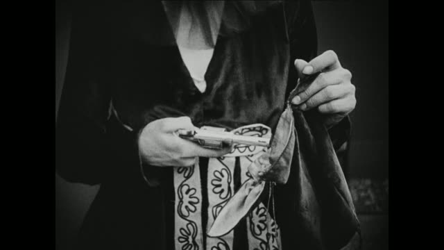 1910s a frantic woman conceals a gun before leaving the house - 1916年点の映像素材/bロール