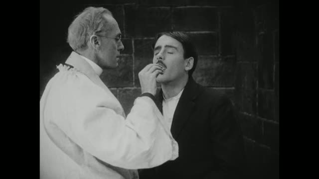 vidéos et rushes de 1910s a man is blessed and given the host ahead of his death sentence - religion
