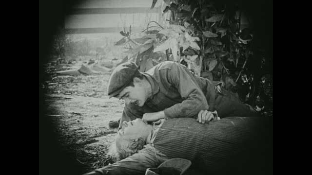 1910s A man watches his comrade die after being injured in a labor riot