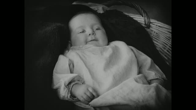 vidéos et rushes de 1910s a melancholy woman plays with her infant - 1910