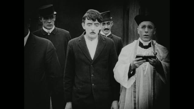 vidéos et rushes de 1910s a priest feels faint as he reads a prisoner his last rights - prêtre
