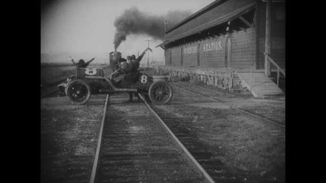 stockvideo's en b-roll-footage met 1910s a speeding car makes a risky move to halt a train - locomotief