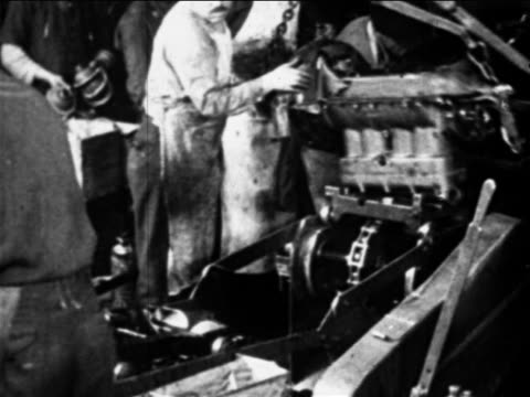 B/W 1910s auto worker moves car engine on assembly line  / Ford factory, Highland Park, MI