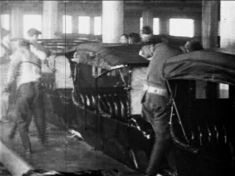 B/W 1910s auto workers building car bodies on assembly line / Ford factory, Highland Park, MI