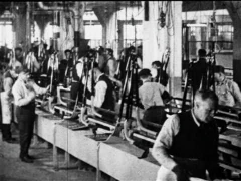 b/w 1910s auto workers working on car parts on assembly line / ford factory, highland park, mi - 自動車産業点の映像素材/bロール
