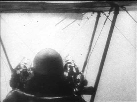 b/w 1910s biplane point of view behind pilot flying behind other plane thru clouds / world war i / newsreel - aereo militare video stock e b–roll