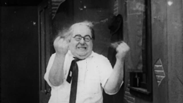 "1910s black and white medium shot stressed-out movie director tearing his hair out in frustration / ""a studio stampede"" - vollglatze stock-videos und b-roll-filmmaterial"