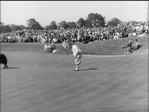 b/w 1910s bobby jones putting into hole in golf tournament as crowd in background cheers / documentary - 1910 stock-videos und b-roll-filmmaterial