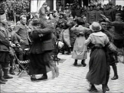 1910s b/w soldiers and women dancing in street as others look on and man plays piano in background / paris, france - prima guerra mondiale video stock e b–roll