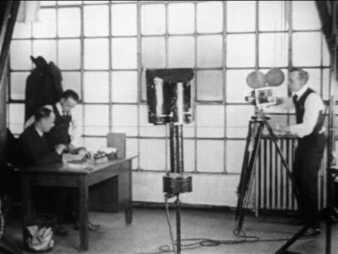 b/w 1910s camerman filming two businessmen at desk / ford film division / documentary - 撮影機材点の映像素材/bロール