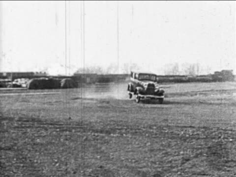 b/w 1910s car bouncing torward camera in test drive on bumpy field / highland park, mi - 試運転点の映像素材/bロール