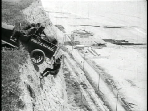 B/W 1910s car with Keystone Kops dangling from cliff edge / closer (2 shots) / feature