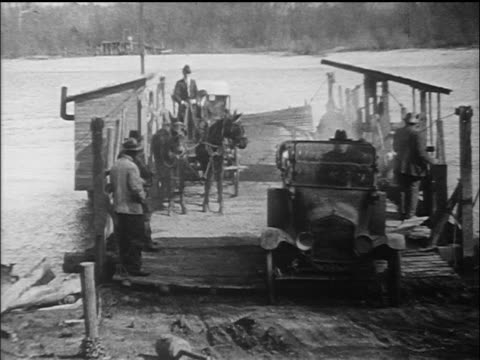 b/w 1910s cars driving off of primitive ferry barge / documentary - ウマ科点の映像素材/bロール
