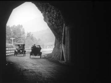 vidéos et rushes de b/w 1910s cars driving thru tunnel / documentary - voiture particulière