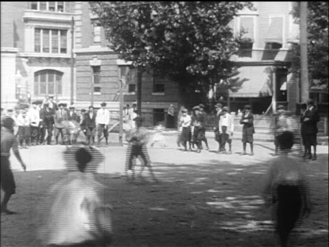 stockvideo's en b-roll-footage met b/w 1910s pan children playing baseball in schoolyard during recess / newsreel - 1915