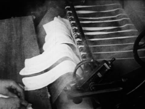 vidéos et rushes de b/w 1910s close up hands of female laundry worker place cloth strips on steaming roller machine / docu. - machinerie