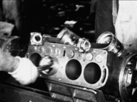 b/w 1910s close up hands of worker put parts into engine on assembly line / ford factory, highland park - ford motor company stock videos and b-roll footage