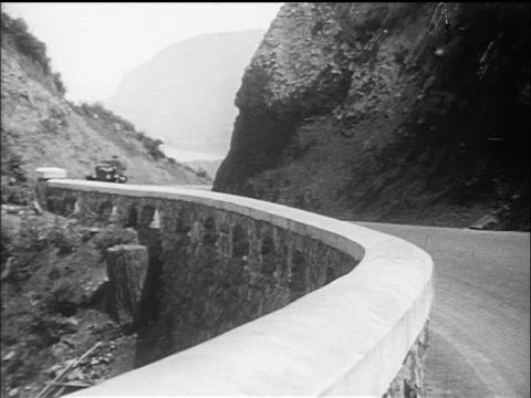 B/W 1910s convertible cars driving up mountain road / documentary