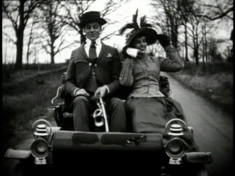 1910s MS Couple driving in early, open car / United States