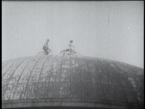 B/W 1910s couple riding bicycles on dome of Palace of Fine Arts / San Francisco