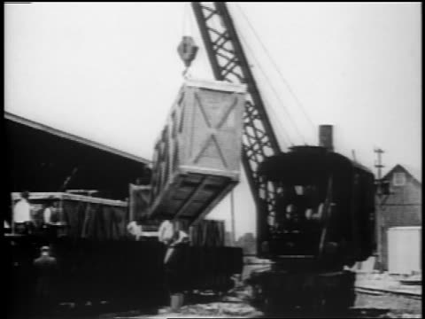 b/w 1910s crane lifting large crate with warplane inside / wwi - holzkiste stock-videos und b-roll-filmmaterial