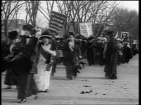 B/W 1910s crowd of women with signs marching in demonstration for suffrage on street