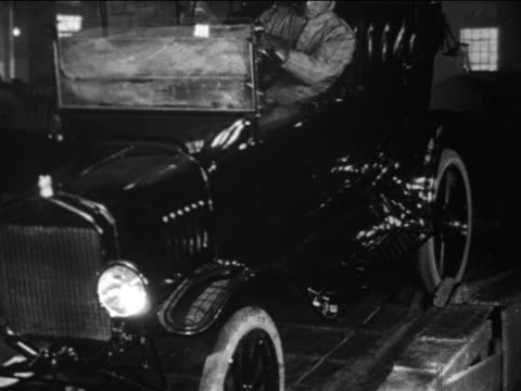 b/w 1910s factory worker drives model t car off of assembly line / ford factory / documentary - ford motor company stock videos and b-roll footage