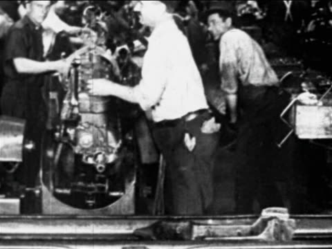 vidéos et rushes de b/w 1910s factory worker moves engine on chain over conveyor belt / ford factory, highland park, mi - ford