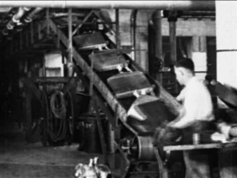 vidéos et rushes de b/w 1910s factory worker with mustache puts grilles on conveyor belt / ford factory, highland park, mi - ford