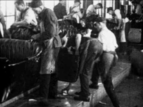 b/w 1910s factory workers cleaning car interiors on assembly line  / ford factory, highland park, mi - ford motor company stock videos & royalty-free footage