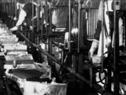 B/W 1910s factory workers' hands place parts on conveyor belt / Ford factory, Highland Park, MI