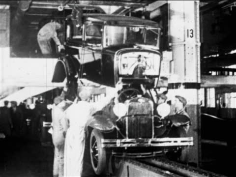 B/W 1910s factory workers lower car body onto chassis on assembly line / Ford factory, MI / indust.
