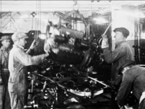 b/w 1910s factory workers lower engine into car on assembly line / ford factory, highland park, mi - ford motor company stock videos & royalty-free footage