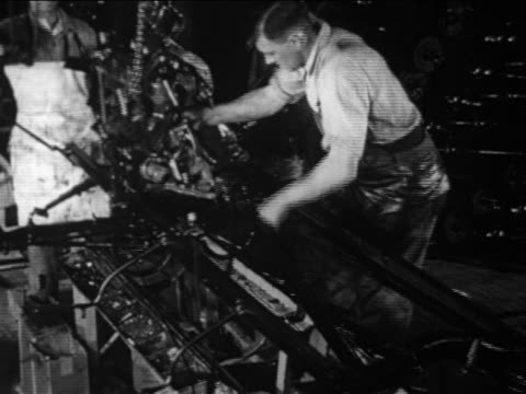b/w 1910s factory workers lower engine into model t chassis on assembly line / documentary - フォード・t型モデル点の映像素材/bロール