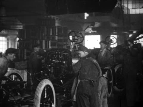 B/W 1910s factory workers lower Model T body onto chassis on assembly line / Ford factory / docu.