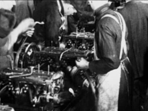 b/w 1910s factory workers work on car engines on assembly line / ford factory, highland park, mi - ford motor company stock videos & royalty-free footage