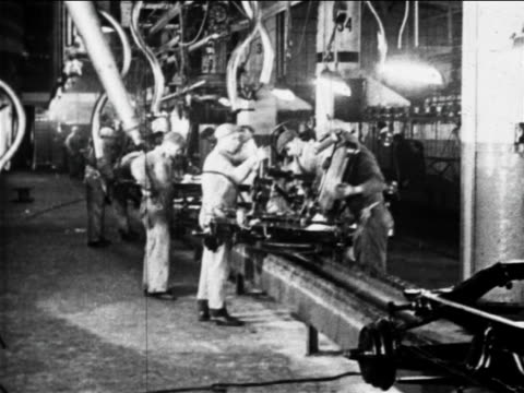 b/w 1910s factory workers work on car on assembly line / ford factory, highland park, mi - automobile industry stock videos & royalty-free footage