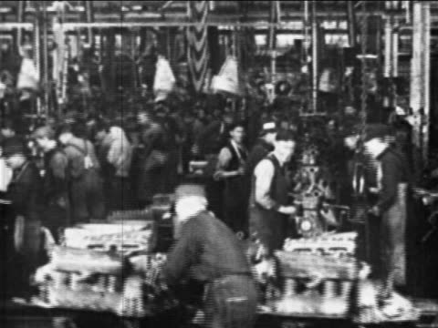 B/W 1910s factory workers work on car parts in assembly line  / Ford factory, Highland Park, MI
