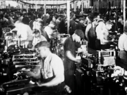 vidéos et rushes de b/w 1910s factory workers work on car parts on assembly line / ford factory, highland park, mi - ford