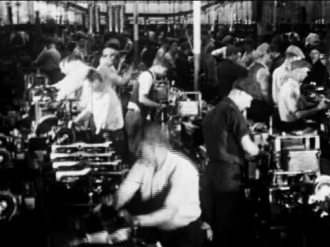 B/W 1910s factory workers work on car parts on assembly line / Ford factory, Highland Park, MI