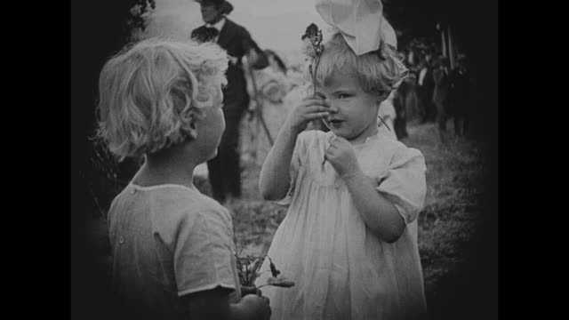 1910s families frolic on a hillside as angels greet from above - 1916年点の映像素材/bロール