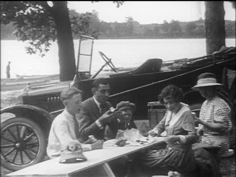 stockvideo's en b-roll-footage met b/w 1910s family eating picnic at table by lake / car in background / documentary - 1915